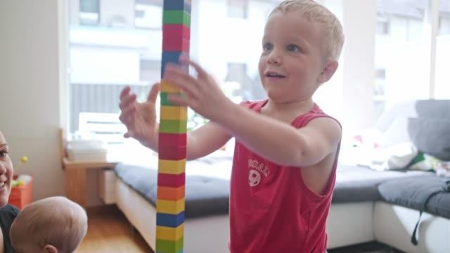 vídeos y material grabado en eventos de stock de torre del edificio del muchacho joven de bloques del juguete - construir