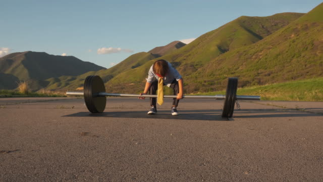 young boy businessman lifting weights - anticipation stock videos & royalty-free footage
