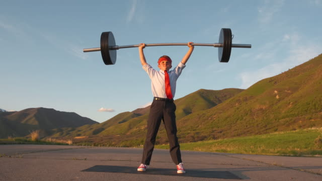young boy businessman lifting weights - solution stock videos & royalty-free footage