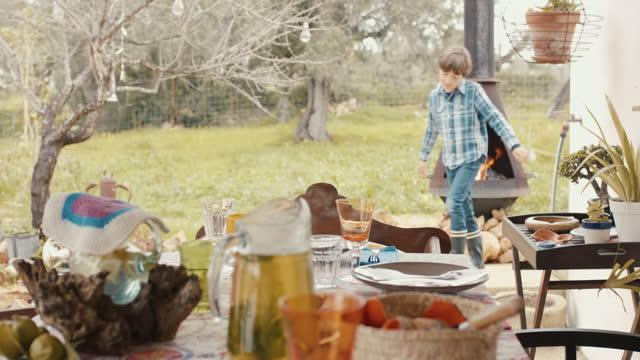 vidéos et rushes de young boy by fireplace and lunch table - préparer à manger