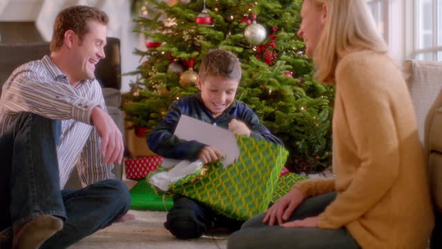 Young boy carefully unwraps and then tears into Christmas present with a frenzy (dolly-shot)