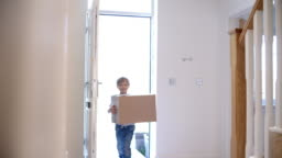 Young Boy Carrying Box Into New Home On Moving Day