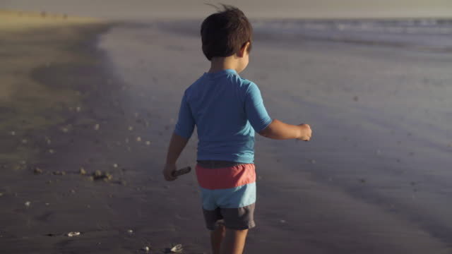 Young Boy Cautiously Walks Across the Sand