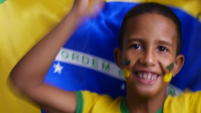 vídeos de stock, filmes e b-roll de menino novo que comemora com bandeira brasileira - incentivo