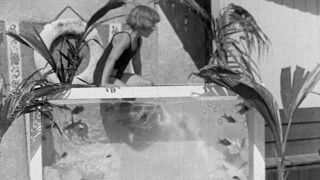 vídeos y material grabado en eventos de stock de b/w young boy climbing into large aquarium with fish swimming - traje de baño de una pieza