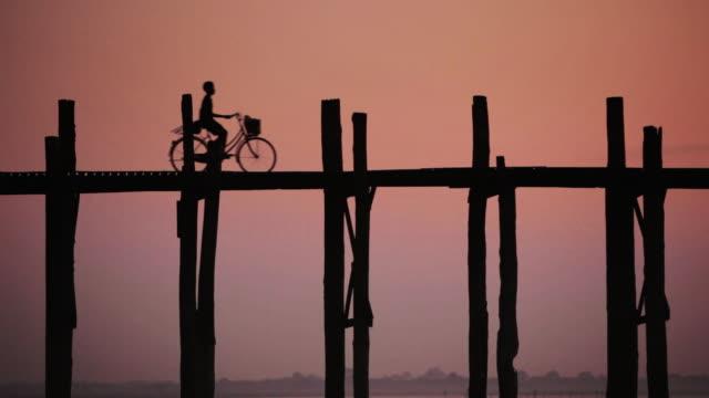 vídeos y material grabado en eventos de stock de ls a young boy cycles across u bein bridge at sunset, the longest teak bridge in the world / mandalay, myanmar - un solo adolescente