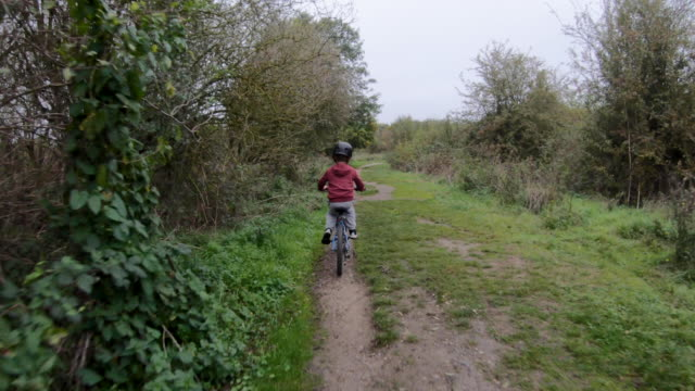 young boy cycling through a park - western europe stock videos & royalty-free footage