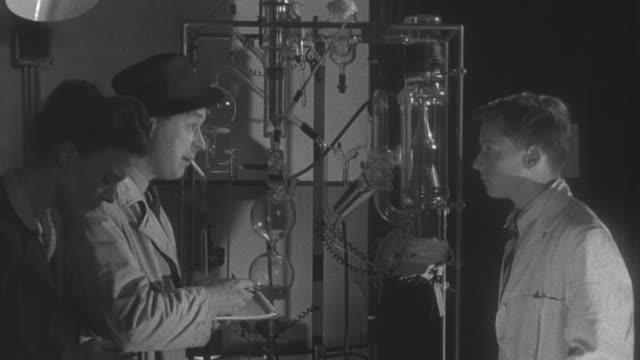 vídeos y material grabado en eventos de stock de 1947 ms young boy daydreaming about being a scientist interviewing with reporters / united kingdom - cámara de televisión