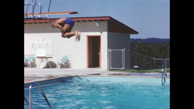 a young boy dives making a back flip into a pool. - バク転点の映像素材/bロール