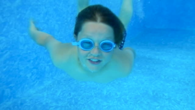 stockvideo's en b-roll-footage met a young boy diving and playing in a swimming pool. - binnenbad