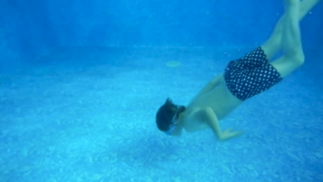 a young boy diving and playing in a swimming pool. - piscina pubblica all'aperto video stock e b–roll