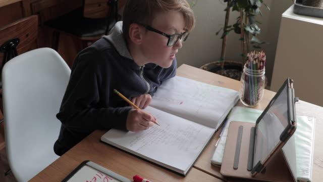 stockvideo's en b-roll-footage met de jonge jongen doet schoolwerk thuis - bril brillen en lenzen
