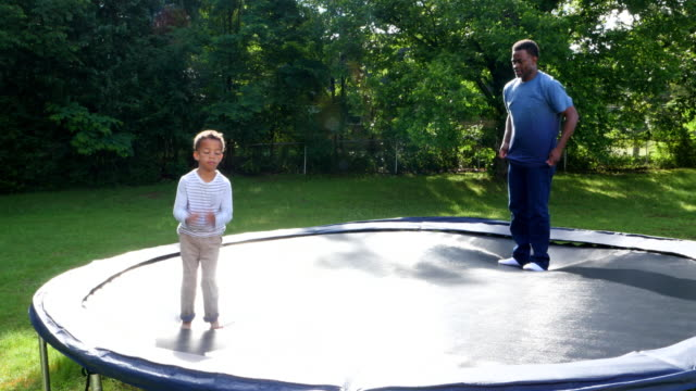 MS Young boy doing flip while playing on trampoline with father in backyard