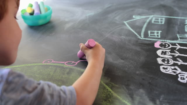 vidéos et rushes de young boy drawing a car using chalks on table, over shoulder view - dessin