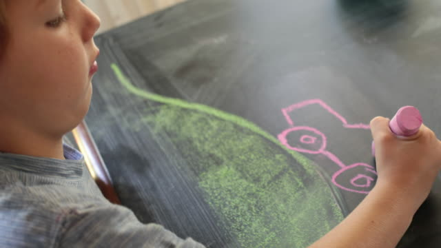 vidéos et rushes de young boy drawing a car using chalks on table, side angle - dessin