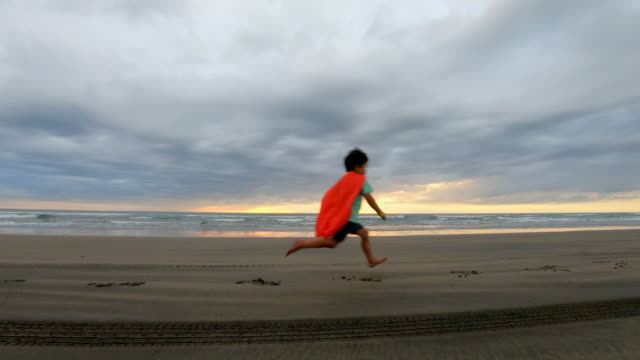 young boy dressed as a super hero running on the beach - heroes stock videos & royalty-free footage