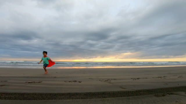 Young Boy Dressed as a Super Hero Running on the Beach
