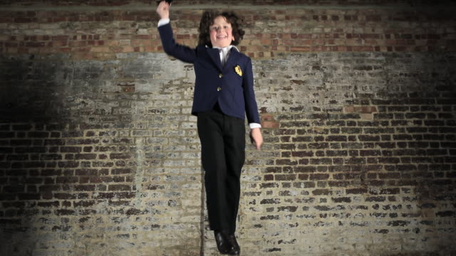 Young boy dressed as sailor jumping up and down