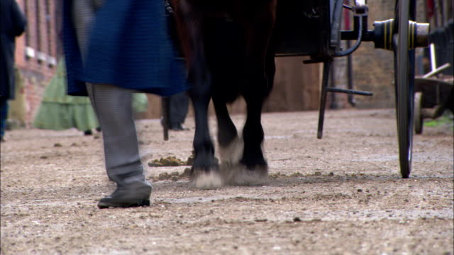 stockvideo's en b-roll-footage met a young boy dressed in 19th century clothing runs behind a horse and carriage. - 19e eeuw