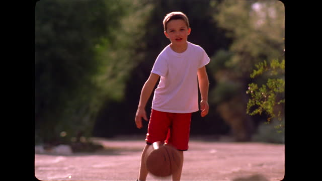 A young boy dribbles a basketball and then walks down a road with his father.