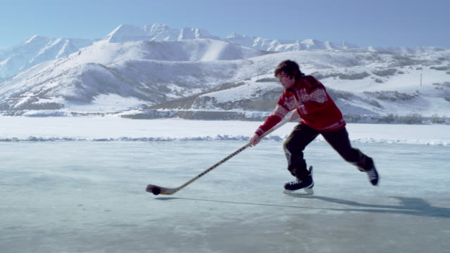 young boy dribbling a hockey puck toward the goal at an outdoor ice rink. - アイスホッケー点の映像素材/bロール