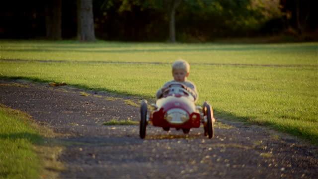 vídeos y material grabado en eventos de stock de young boy driving toy car along gravel path - juguete