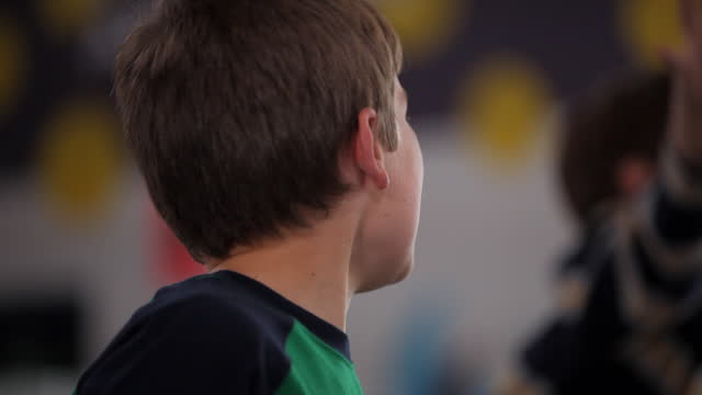 stockvideo's en b-roll-footage met a young boy drums on his desk and cheers during class. - vreugde