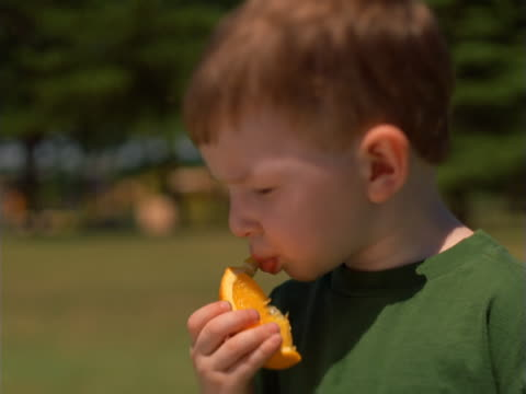 Young boy eating an orange.
