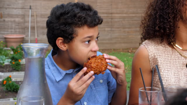 ms young boy eating fried chicken while sitting next to mother at family dinner party - südliche bundesstaaten der usa stock-videos und b-roll-filmmaterial