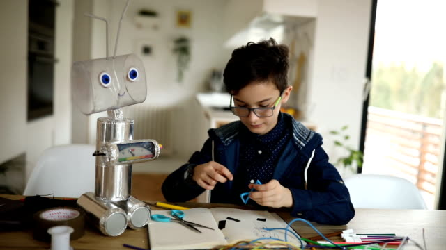 young boy engineer constructing a robot at home - costruire video stock e b–roll