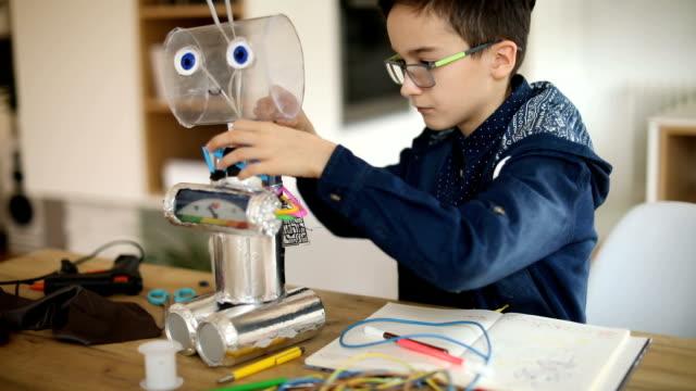 vidéos et rushes de ingénieur jeune garçon faisant un robot - réparer