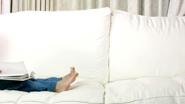 hd: junge, die lektüre auf dem sofa couch - schulkind nur jungen stock-videos und b-roll-filmmaterial