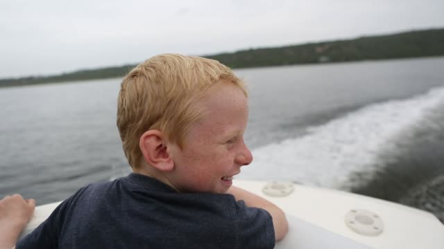 young boy enjoys riding on the speedboat - motorboat stock videos & royalty-free footage