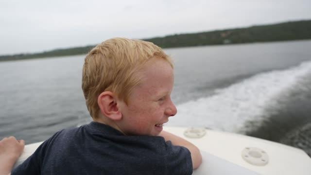 vidéos et rushes de jeune garçon bénéficie d'équitation sur le hors-bord - bateau à moteur