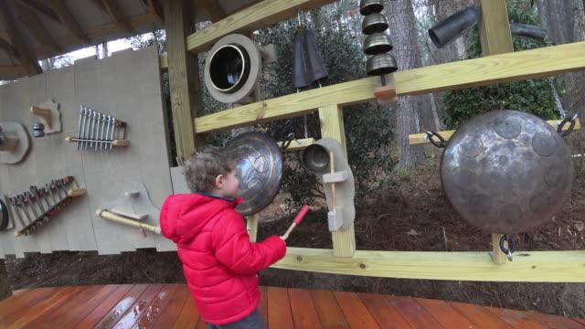 vídeos de stock e filmes b-roll de young boy experimenting with instruments in a soundscape - exposição