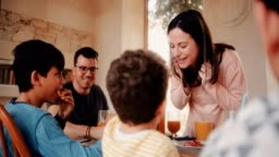 Young boy feeding mother pancake during breakfast with family