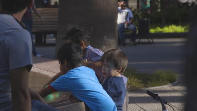vídeos de stock e filmes b-roll de young boy fills water bottles in fountain, medium shot - pobreza questão social