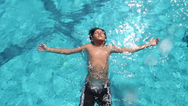 ws young boy floating on back  on pool surface/singapore - galleggiare sull'acqua video stock e b–roll