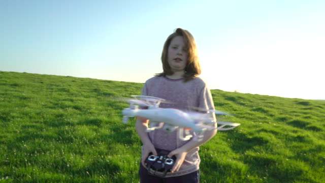 a young boy flying a drone in an empty field. - radio controlled handset stock videos and b-roll footage
