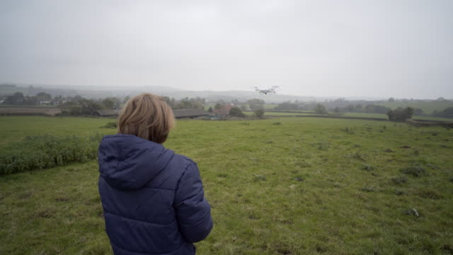 a young boy flying a drone - ein junge in gummistiefel stock-videos und b-roll-filmmaterial