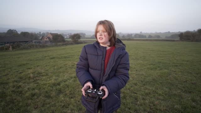 stockvideo's en b-roll-footage met a young boy flying a drone - middellang haar