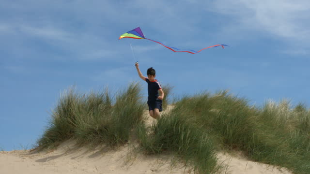 A young Boy flying his kite jumps from a sand dune and smiles having fun.