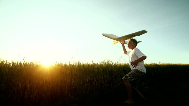 stockvideo's en b-roll-footage met young boy flys an airplane in the country - aspiraties