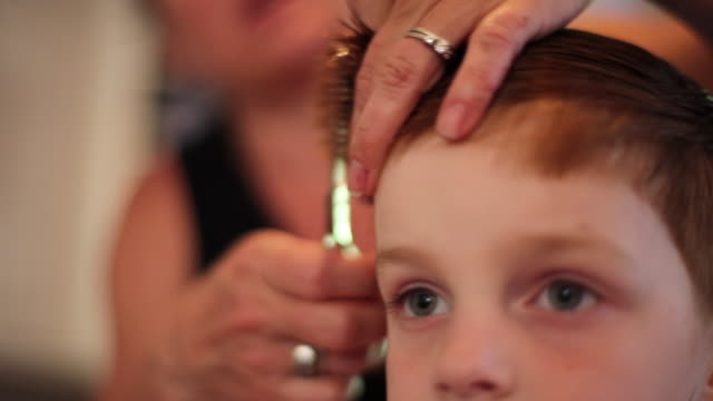Young boy gets hair combed and trimmed with scissors by mom in family kitchen