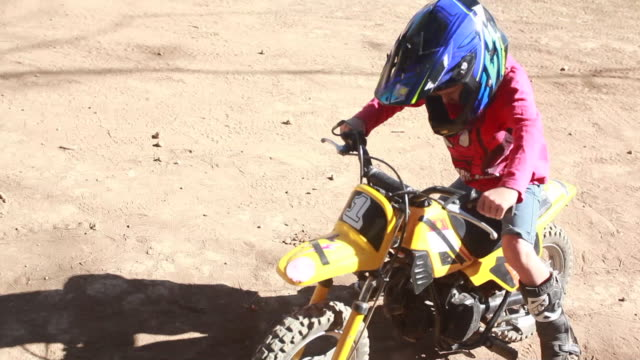 vídeos y material grabado en eventos de stock de young boy getting on a dirt bike while other boys are riding their dirt bikes around a race track behind him on a sunny summer day - kelly mason videos
