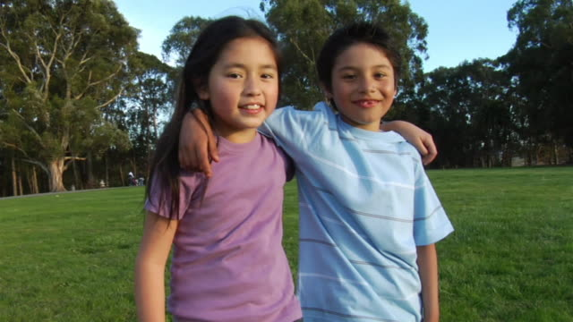 ms pan young boy & girl smiling and standing with arms over each other's shoulders / richmond, california, usa - hugging tree stock videos and b-roll footage
