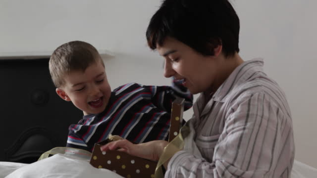 young boy gives mum a present in bed and helps her to open it/uk - zärtlich stock-videos und b-roll-filmmaterial