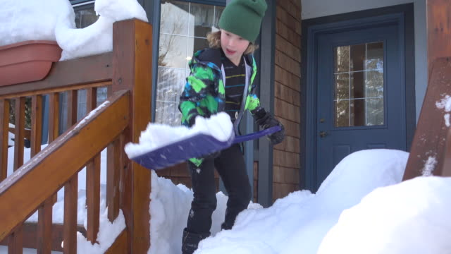 young boy happily shoveling snow off a porch - digging stock videos and b-roll footage