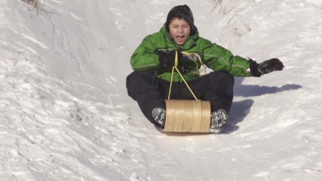 young boy has fun sledding on a sunny winter day - falla av bildbanksvideor och videomaterial från bakom kulisserna