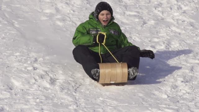 young boy has fun tobogganing - falla av bildbanksvideor och videomaterial från bakom kulisserna